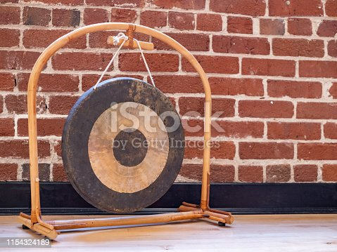 Small suspended gong sitting on wooden floor against a brick wall backdrop
