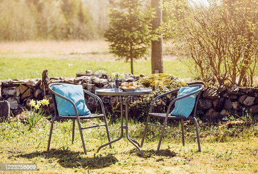 Small table set in rural home garden with chairs and table for two, freshly baked pastries on table, sunny spring morning. Stacked stone fence wall on background. Blurred field and forest.