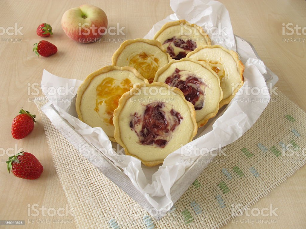 Small tartlets with fresh cheese, peach and strawberry stock photo