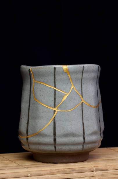 Small tea cup with kintsugi repair. A small handmade tea cup that I repaired using the Japanese art form of kintsugi and a gold powder. pottery stock pictures, royalty-free photos & images