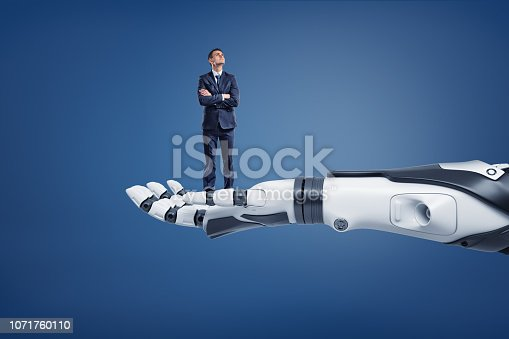 A small thinking businessman looks up while standing on a huge robotic arm. Regarding new technologies. Business and high-tech. Scientific progress in office.
