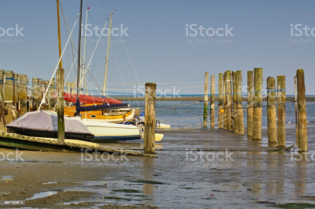 Small tidal harbour at low tide with various sailboats between mooring posts stock photo