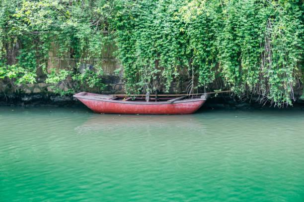 Un pequeño bote de lata en el río de la ciudad - foto de stock
