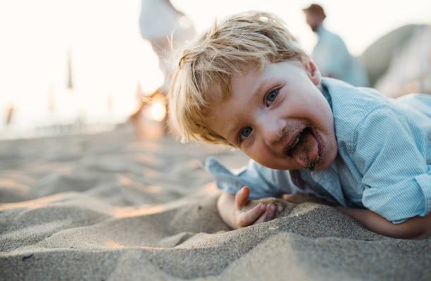 a small toddler boy standing on beach on summer holiday, having fun. - boca suja imagens e fotografias de stock