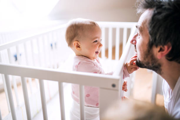 A small toddler girl standing in cot with her father at home. stock photo