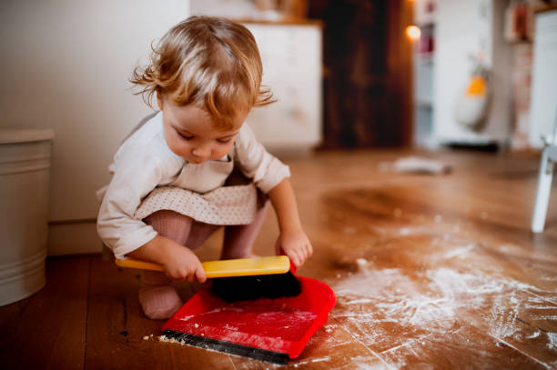 a small toddler girl with brush and dustpan sweeping floor in the kitchen at home. - sweeping stock pictures, royalty-free photos & images