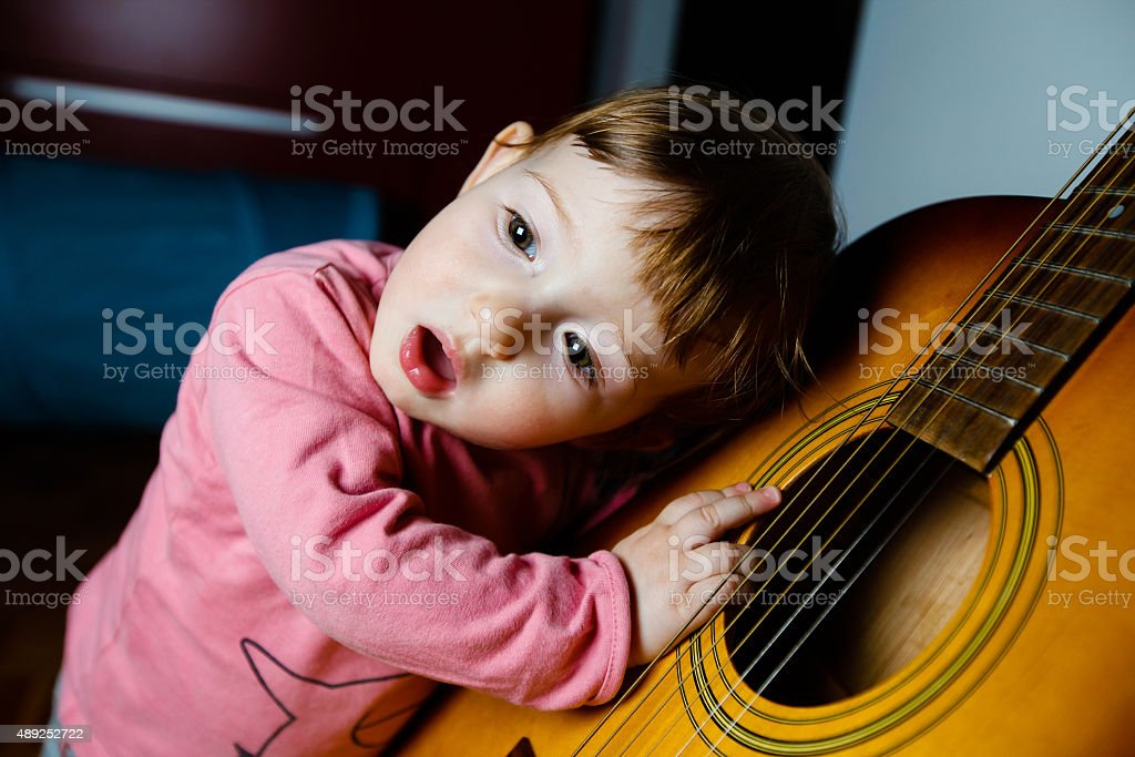 Small toddler listening to sound of a guitar stock photo
