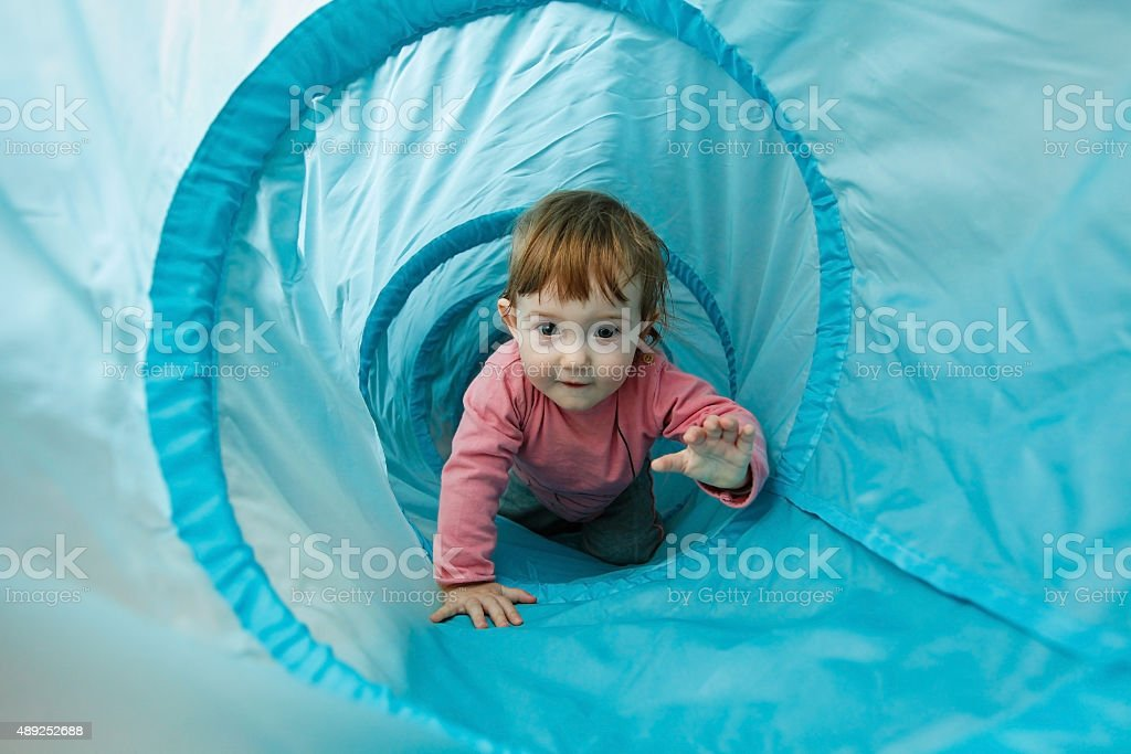 Small toddler playing in a tunnel tube stock photo