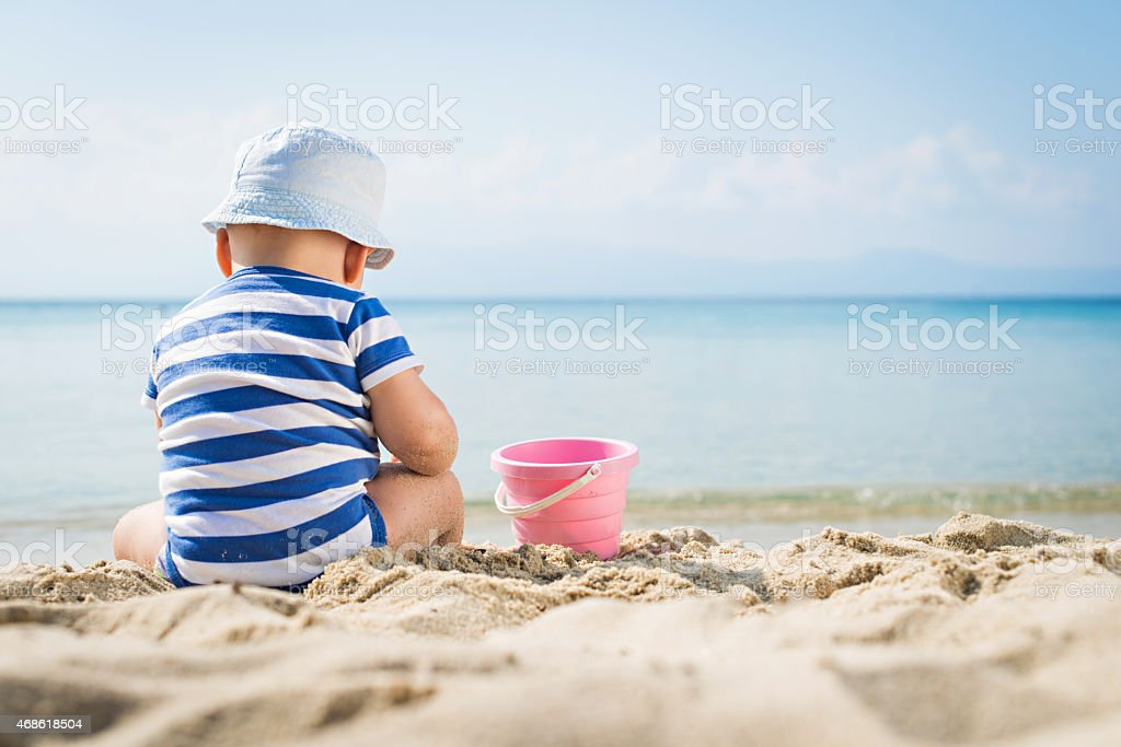 Small toddler playing in the sand stock photo