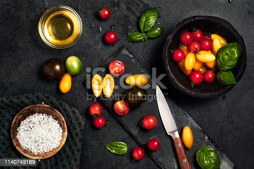 A variety of tomatoes on a board with a knife and rock salt
