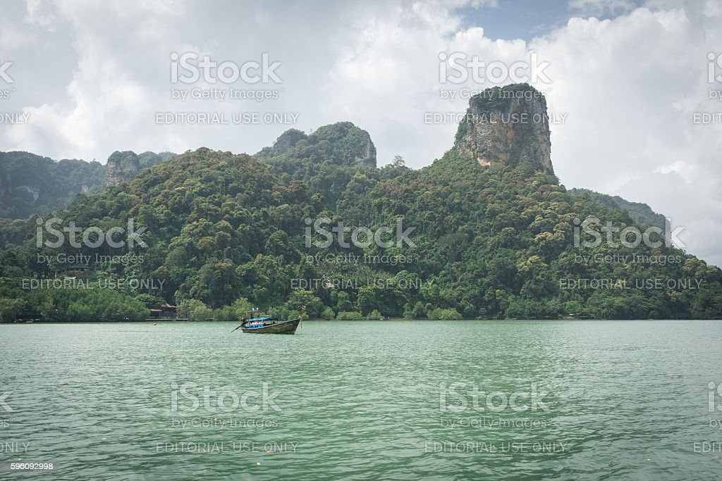 Small tourist boat in sea under mountain and cloudy sky royalty-free stock photo