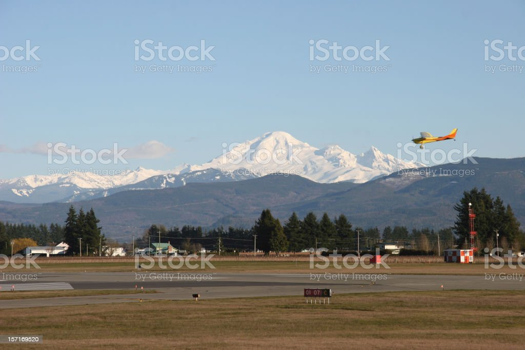 Small Town Airport with Plane and Snowcapped Mountain stock photo