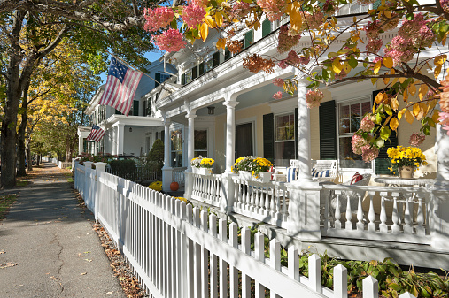 A view of some antique houses, dappled with warm autumn sunlight, in the charming town of Woodstock, Vermont.