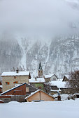 Small Town at the foot of the high mountains on a winter overcast day with low clouds. France, Savoie, Bessans