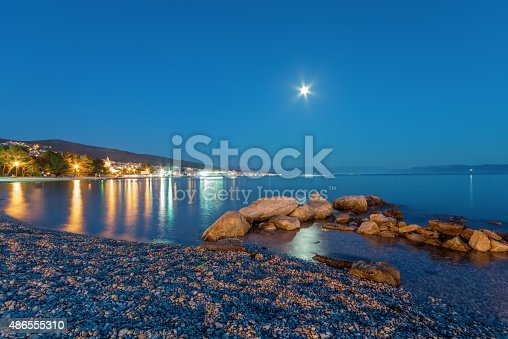 istock Small town by the sea at night 486555310