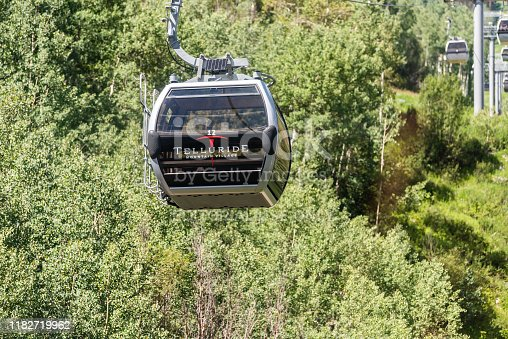 Telluride, USA - August 14, 2019: Small town in Colorado with closeup of free gondola to mountain village in summer riding with cables by green trees