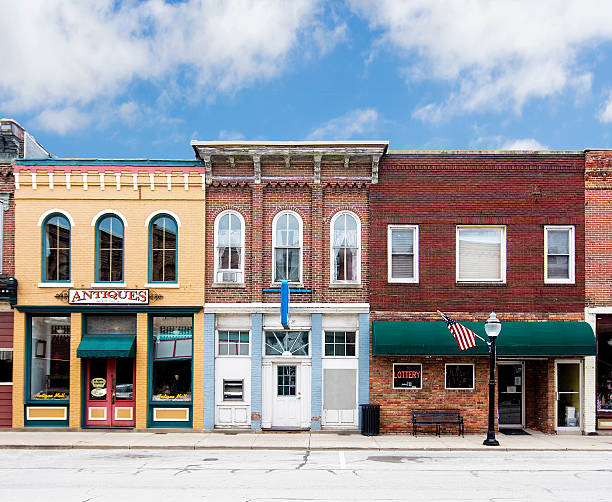 Small Town Main Street A photo of a typical small town main street in the United States of America. Features old brick buildings with specialty shops and restaurants. Decorated with  American flags. americana stock pictures, royalty-free photos & images