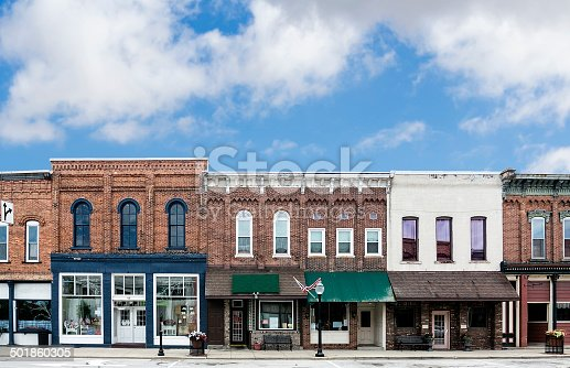 A photo of a typical small town main street in the United States of America. Features old brick buildings with specialty shops and restaurants. Decorated with spring flowers and American flags.