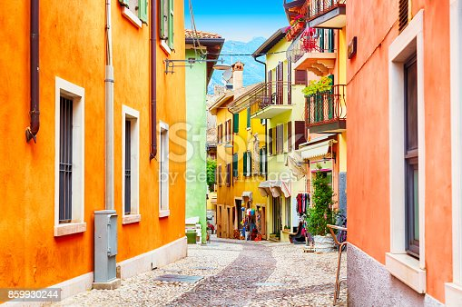 istock Small town narrow street view with colorful houses in Malcesine, Italy during sunny day. Beautiful lake Garda. 859930244