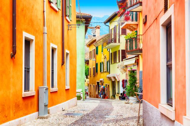 cidade pequena estreita rua vista com casas coloridas em malcesine, itália durante o dia de sol. lindo lago garda. - lombardia - fotografias e filmes do acervo