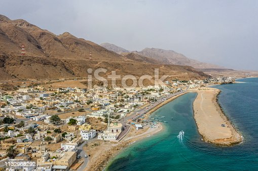 Small Oman town Tiwi, captured from air. A mountain range is visible rising behind the town.
