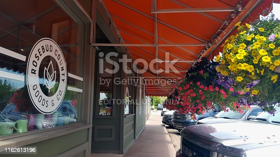 Rosebud,Alberta, Canada- July 10,2019: Shops on Main Street of Rosebud Alberta. Orange Canopy awning with hanging baskets of flowers. Cars parked.