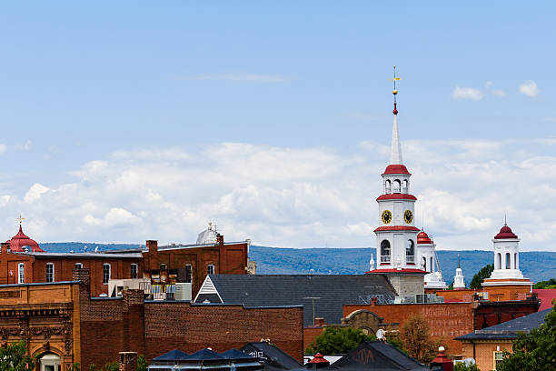 small town steeples and rooftops, mountains in background - torenspits stockfoto's en -beelden