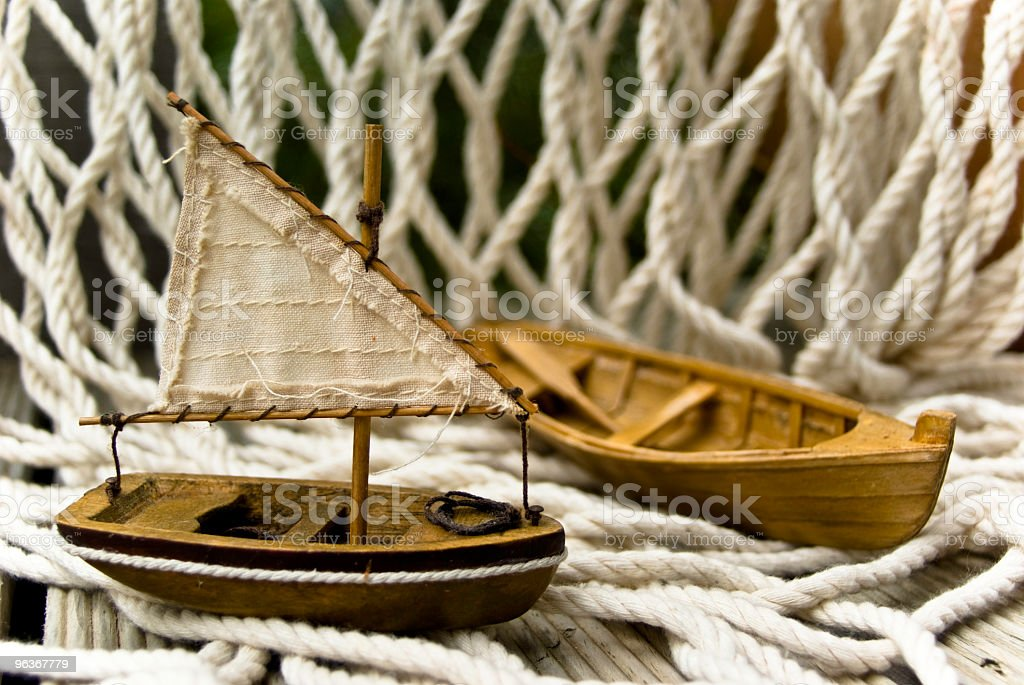 Small toy boats on wooden deck with old fishing net royalty-free stock photo