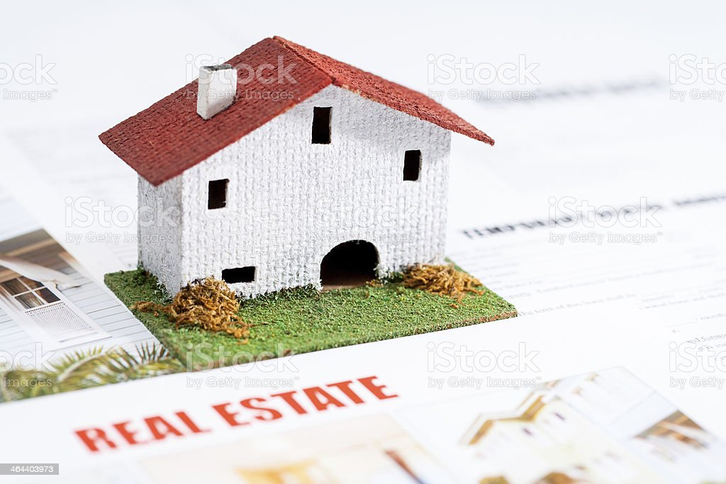 Small toy house on real estate documents. stock photo