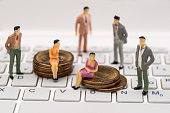 Small toy people are standing on a laptop and sitting on coins .