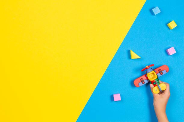 Kleine Spielzeug-Flugzeug in Kinderhänden und bunte Holzwürfel auf blauem und gelbem Hintergrund – Foto