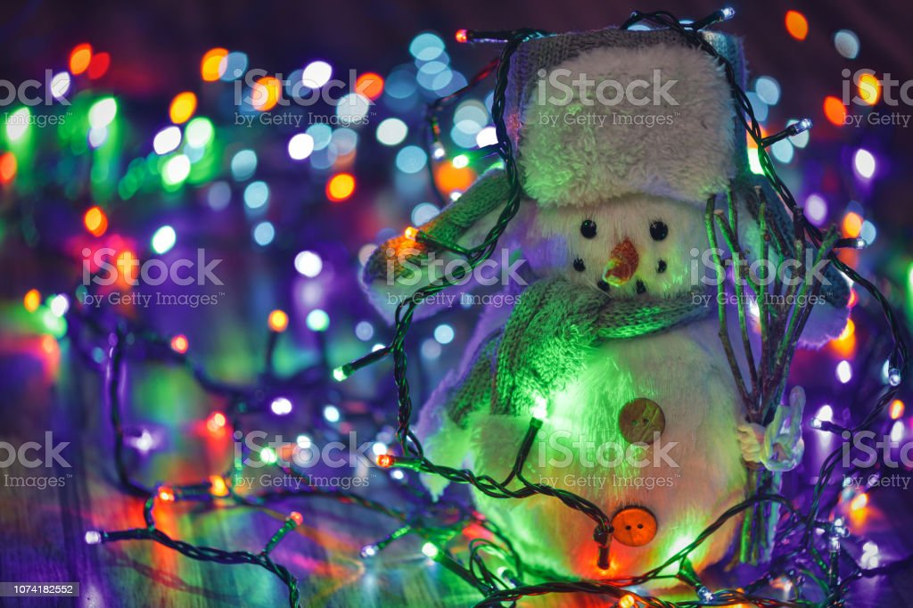 Colorful Christmas Lights Background.Small Toy Snowman On Colorful Christmas Lights Background