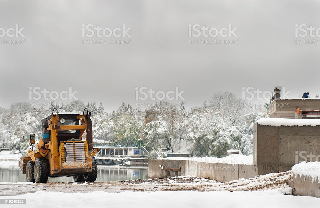small tractor bulldozer in the construction of   building in winter stock photo