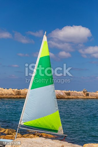 Small triangle sail yellow, green and white color, in Jaffa bay on the Mediterranean Sea