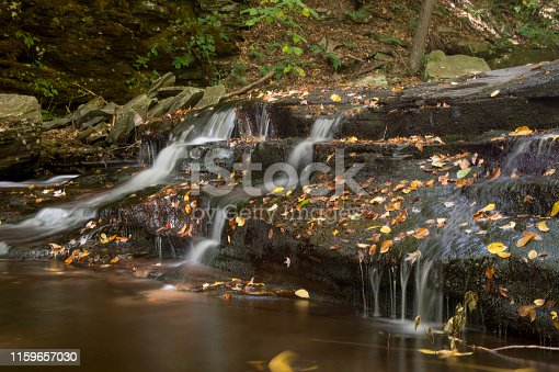 A small trio of waterfalls cascade into a pool of water with autumn colored leaves laying on the rocks.