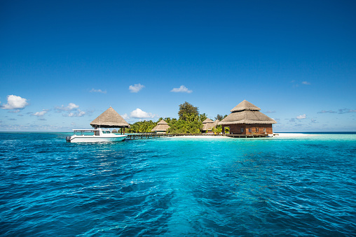 istock small tropical island with Beach Villas and speed boat 467040628