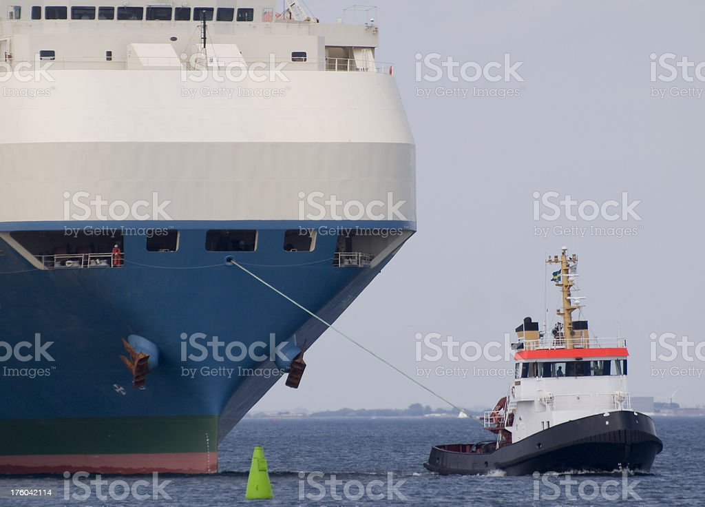Close up view of a large automobile carrier towed into harbor by a...