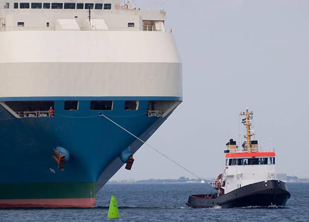 Der kleine Schlepper Abschleppen ein großes Schiff. – Foto