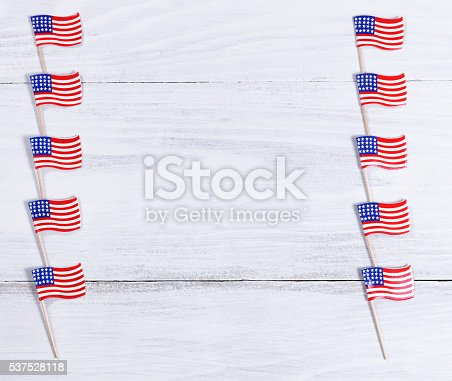 518726782 istock photo Small USA flags on each sides of white wooden boards 537528118