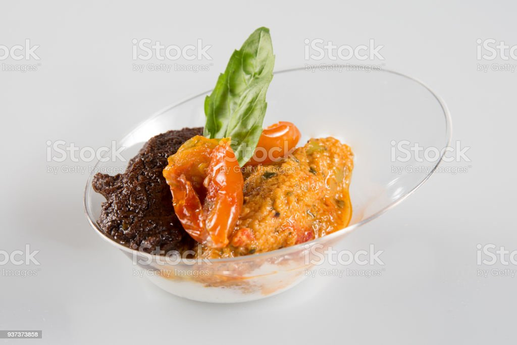 small Verrine with tomatoes and tapenade on a white background stock photo