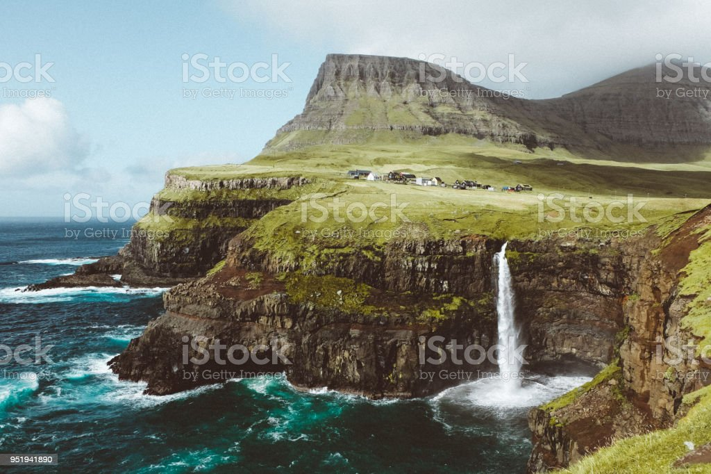 Small village above one of themes beautiful waterfalls in the world on Faroe Islands stock photo