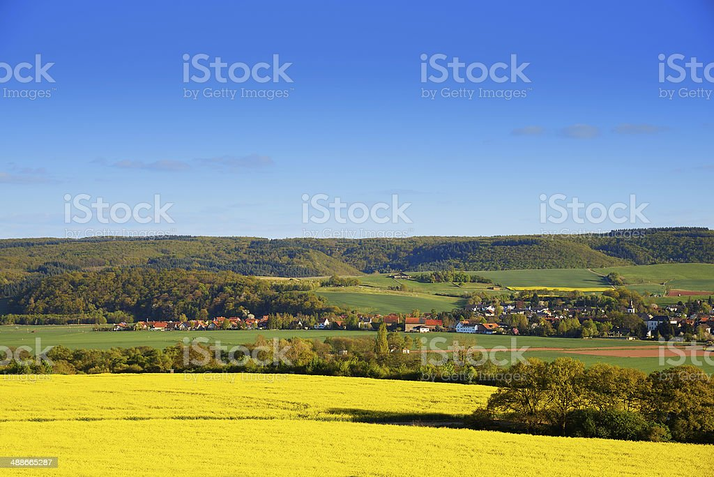 Small village in valley with blooming canola fields royalty-free stock photo