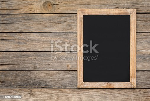 639376084 istock photo Small vintage blank chalkboard on an old wooden background 1188234566
