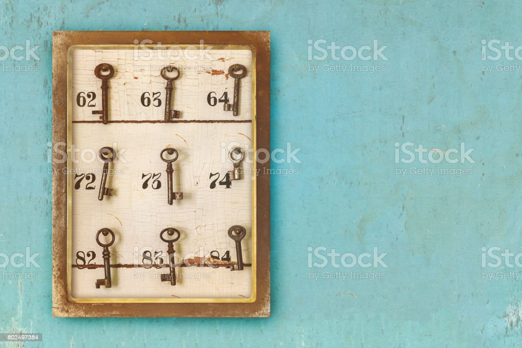 Small vintage cabinet with rusted hotel keys and room numbers stock photo