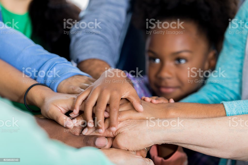Small volunteer puts hands together in unity with adult volunteers stock photo
