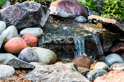 Small water fountain waterfall closeup in garden park with rock pond and colorful stones in Colorado