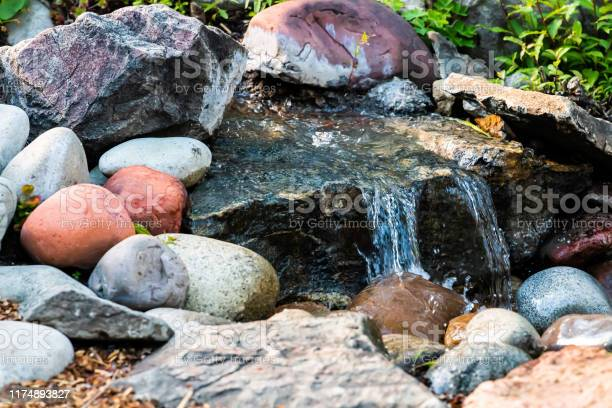 Photo of Small water fountain waterfall closeup in garden park with rock pond and colorful stones in Colorado