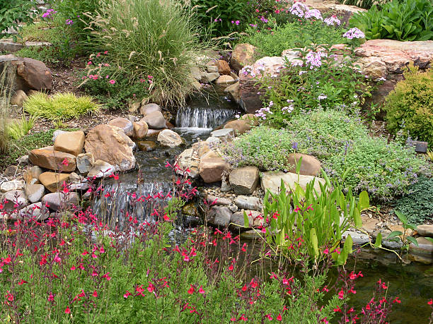 Small Waterfall and Hardscape with Rocks and Flowers stock photo