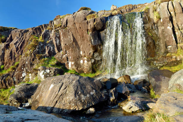 Small waterfall at the Conor Pass, one of the highest Irish mountain passes served by an asphalted road, located on the Dingle Peninsula, County Kerry, Ireland stock photo