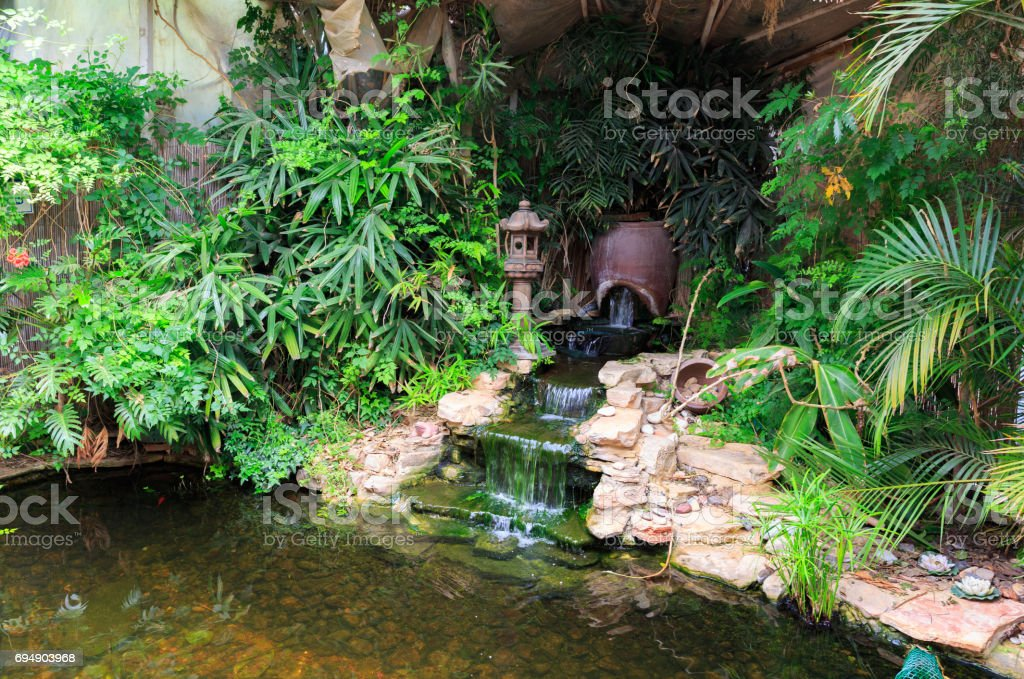 Small waterfall in decorative pond stock photo